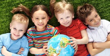Group of happy children lying on a green grass with globe